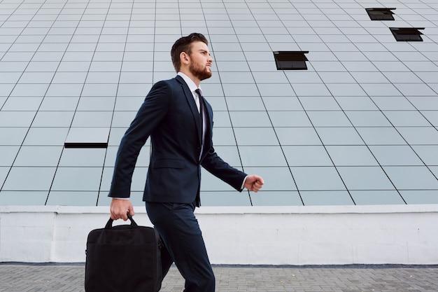 ビジネスマンは、ビジネスbuの背景にバッグを持って歩いています
