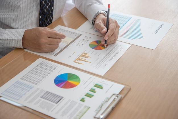 Бизнесмен работает в современном офисе с карандашом, просматривая финансовую отчетность и соответствующие отчетные документы для оценки эффективности бизнеса или возврата инвестиций