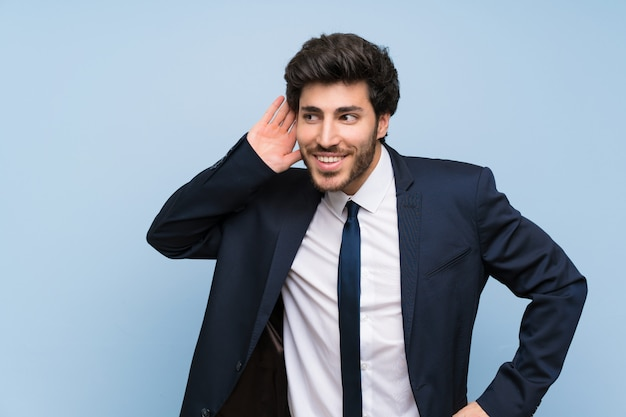 Businessman over isolated blue wall listening to something by putting hand on the ear
