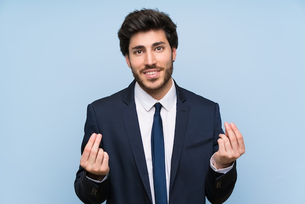 Businessman over isolated blue wall making money gesture