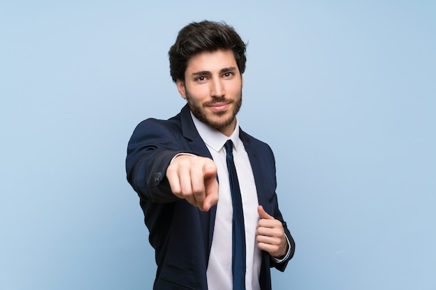Businessman over isolated blue wall points finger at you with a confident expression
