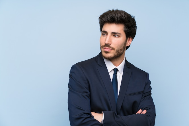 Businessman over isolated blue wall portrait