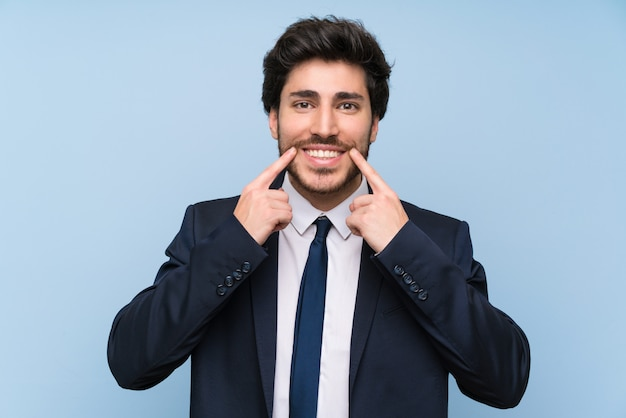 Businessman over isolated blue wall smiling with a happy and pleasant expression