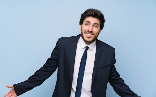 Businessman over isolated blue wall smiling