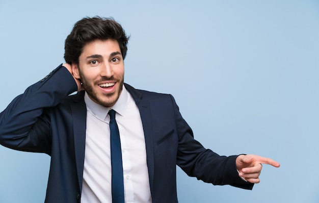 Businessman over isolated blue wall surprised and pointing finger to the side