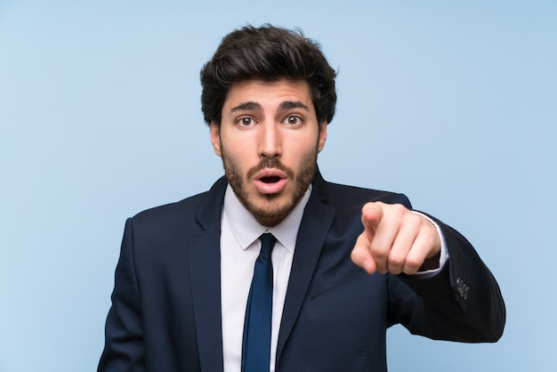 Businessman over isolated blue wall surprised and pointing front
