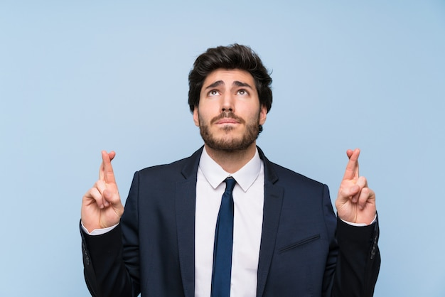 Businessman over isolated blue wall with fingers crossing and wishing the best