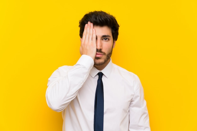 Businessman on isolated yellow covering a eye by hand