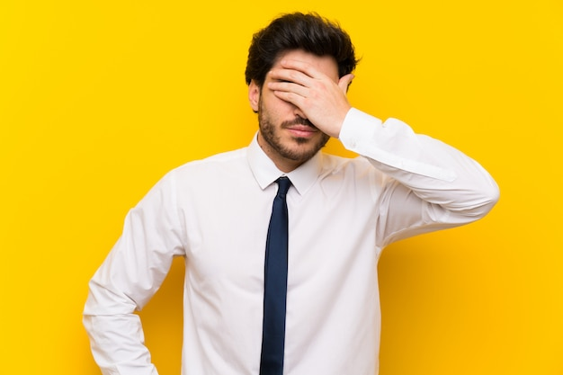 Businessman on isolated yellow covering eyes by hands
