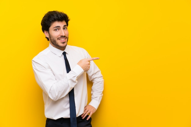 Businessman on isolated yellow pointing finger to the side