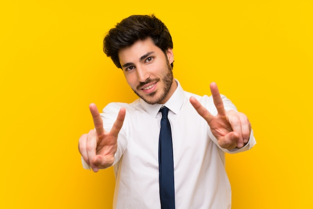 Businessman on isolated yellow  smiling and showing victory sign