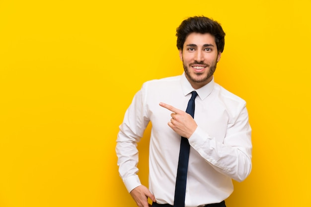 Businessman on isolated yellow wall pointing finger to the side