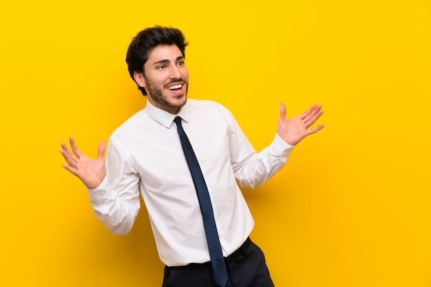 Businessman on isolated yellow with surprise facial expression