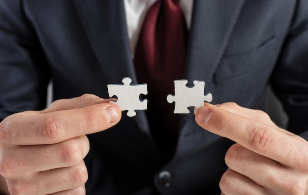 Businessman join two puzzle pieces. concept of teamwork and partnership.