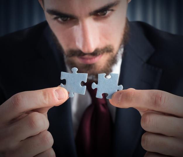 ビジネスマンはパズルの 2 つのピースを結合します。