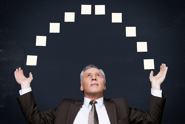 Businessman juggling. confident senior man in formalwear juggling with adhesive notes while standing against blackboard