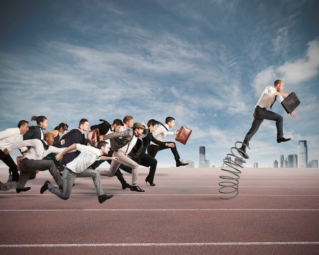 Бизнесмен прыгает на пружине во время гонки с противниками