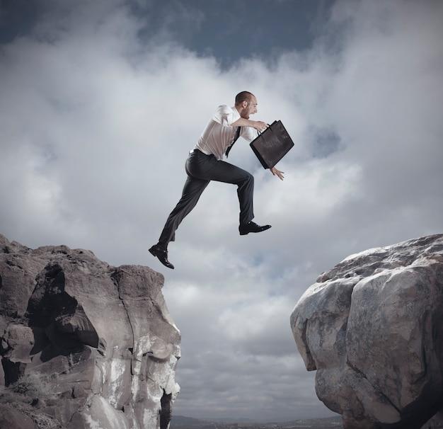 山を飛び越えるビジネスマン