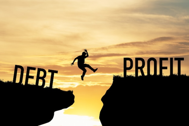 Businessman jumping over two cliffs between debt and profit. it is symbol of business investment target concept.
