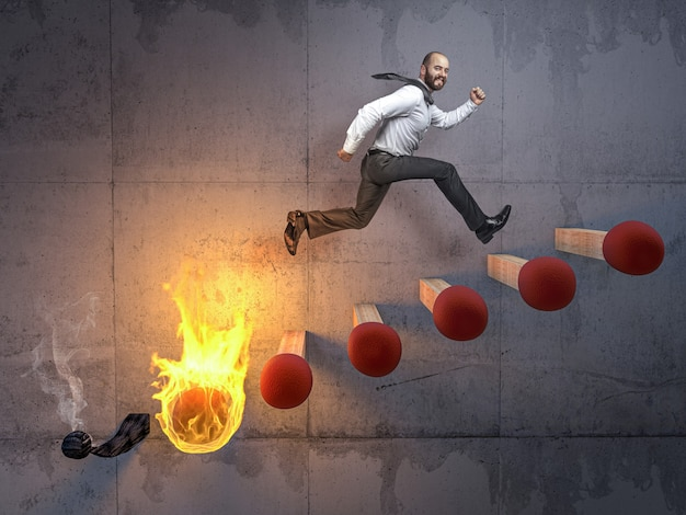 Businessman jumps on a stair made of matches that are about to catch fire.