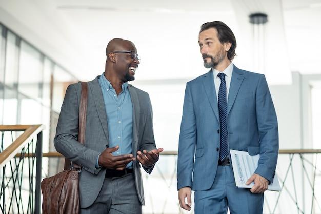 웃 고 사업가입니다. 회색 머리 동료와 이야기하면서 웃고 있는 검은 피부의 사업가