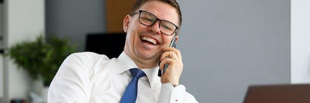 Бизнесмен смеется разговаривает по телефону с партнером
