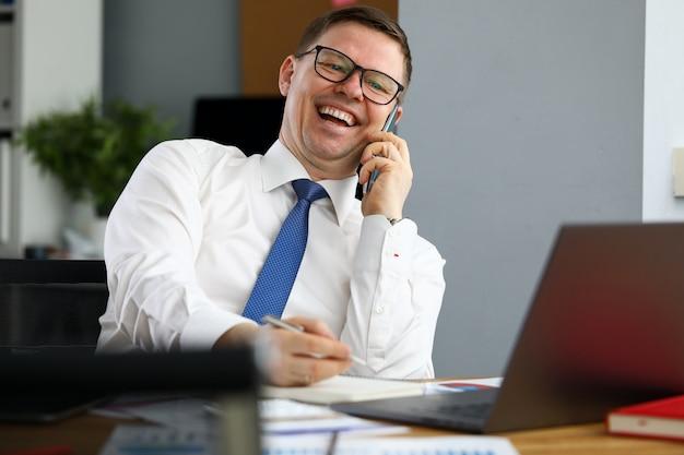 パートナーと電話で話している笑いの実業家