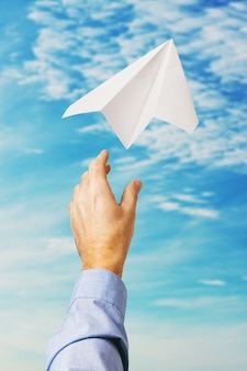Businessman launched a paper airplane in the sky as a symbol of new business
