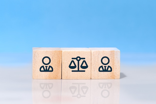 Businessman and of law icons on wooden cubes against blue background. concept of lawsuit, judicial conflict, dispute or prosecution in business