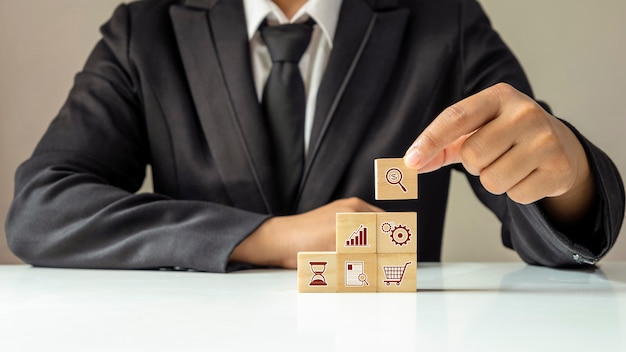 Businessman laying out the financial business icon on the wooden cube