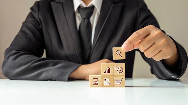 나무 큐브에 금융 비즈니스 아이콘을 배치하는 사업가