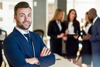 Businessman leader in modern office with businesspeople working