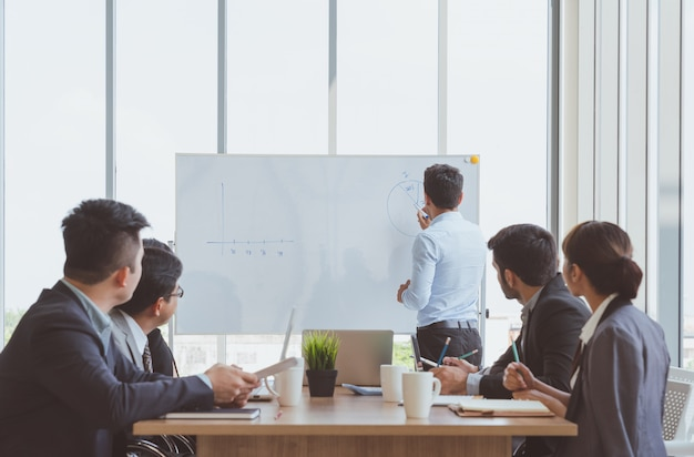 Бизнесмен лидер, писать на доске представить бизнес-маркетинг график во время встречи с коллегами в офисе. презентация совещания бизнес-группы, бизнес-концепция планирования конференции