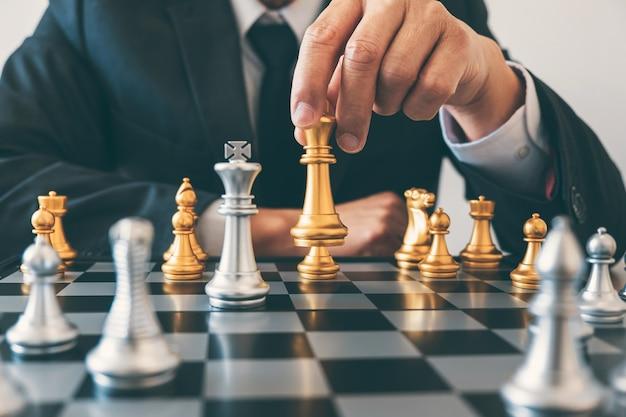 Руководство бизнесмена играет в шахматы и обдумывает стратегический план о крахе, чтобы свергнуть противоположную команду и проанализировать развитие для успешного корпоративного.