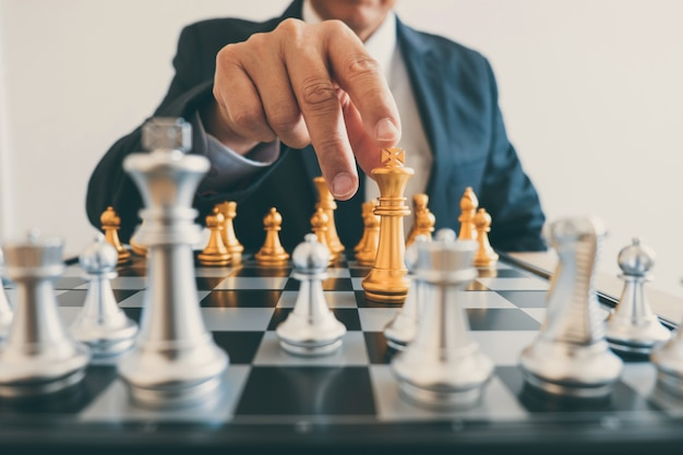 Businessman leadership playing chess and thinking strategy plan about crash overthrow opposite team