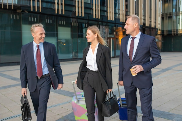 Businessman leading foreign colleagues. businesspeople walking at office building, wheeling suitcases, talking. business trip concept