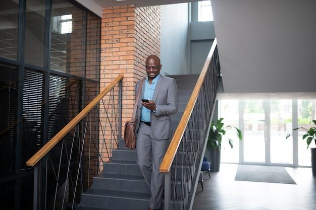 Бизнесмен, покидая офис. темнокожий бизнесмен выходит из офиса и читает сообщение по телефону