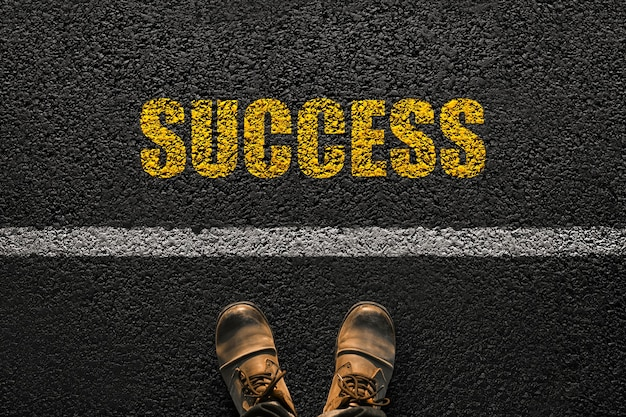 Businessman legs with shoes goes on the asphalt with yellow text success, top view. career development concept