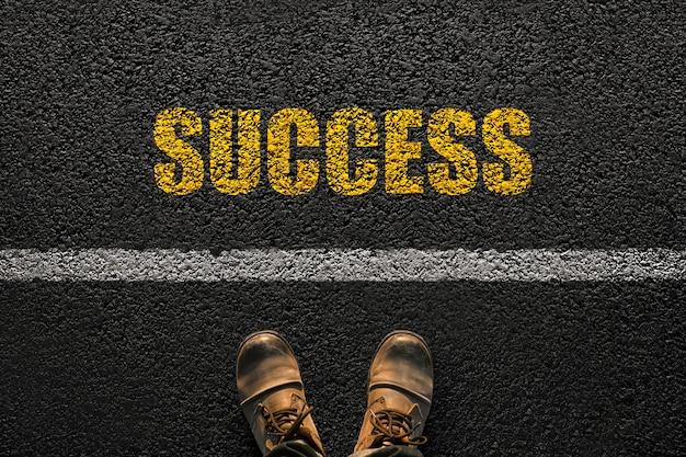 靴を履いたビジネスマンの足は黄色のテキストでアスファルトに行きます成功、上面図。キャリア開発のコンセプト