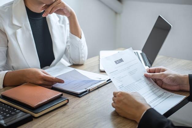 Бизнесмен прислушивается к ответам кандидата, объясняющим его профиль и коллоквиумную работу мечты