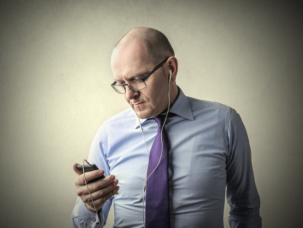 Businessman listening to music on earphones