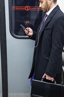 Businessman listening to music in subway train