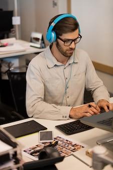 창조적 인 사무실에서 일하는 동안 헤드폰을 통해 사업가 듣는 음악