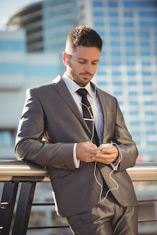 Businessman listening to music and using
