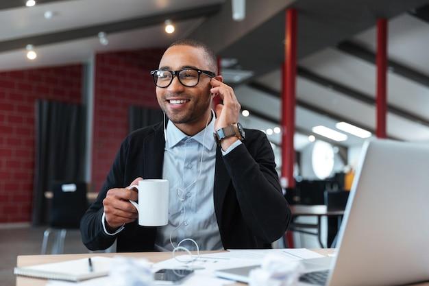 Бизнесмен, слушающий музыку и держащий чашку в офисе