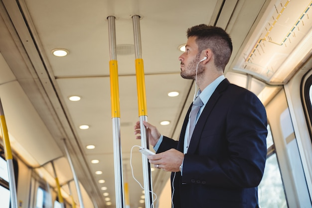 Бизнесмен слушает музыку и использует на мобильном телефоне