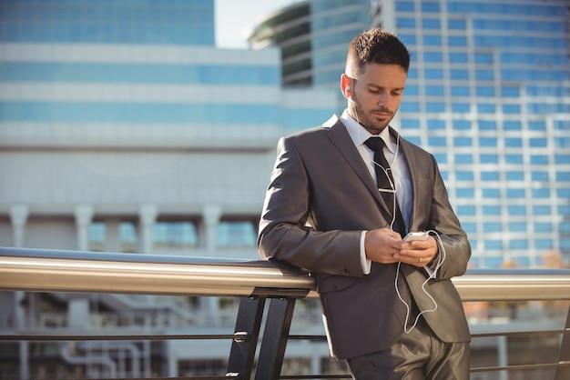 Бизнесмен слушает музыку и использует