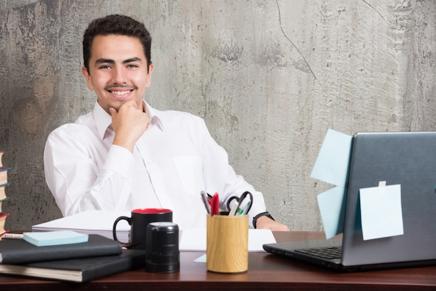 Бизнесмен, глядя на камеру с счастливым выражением на офисном столе.