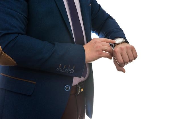 ビジネスマンは、白い背景で隔離のビジネス会議の前に時計を見て