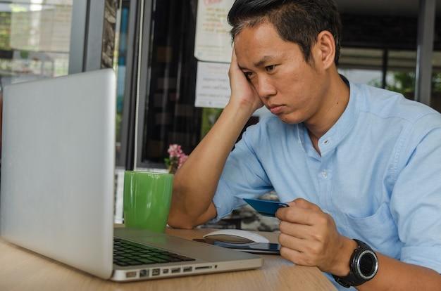 Бизнесмен, глядя на кредитные карты, проверяя расходы по долгу